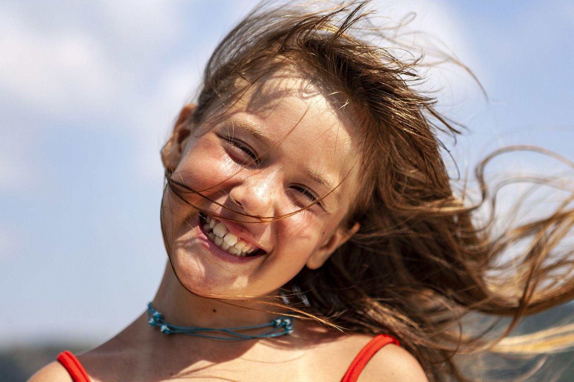 niña sonriendo antes de hacer un tratamiento de ortodoncia infantil. Cuando poner aparatos en niños? empezar ortodoncia?
