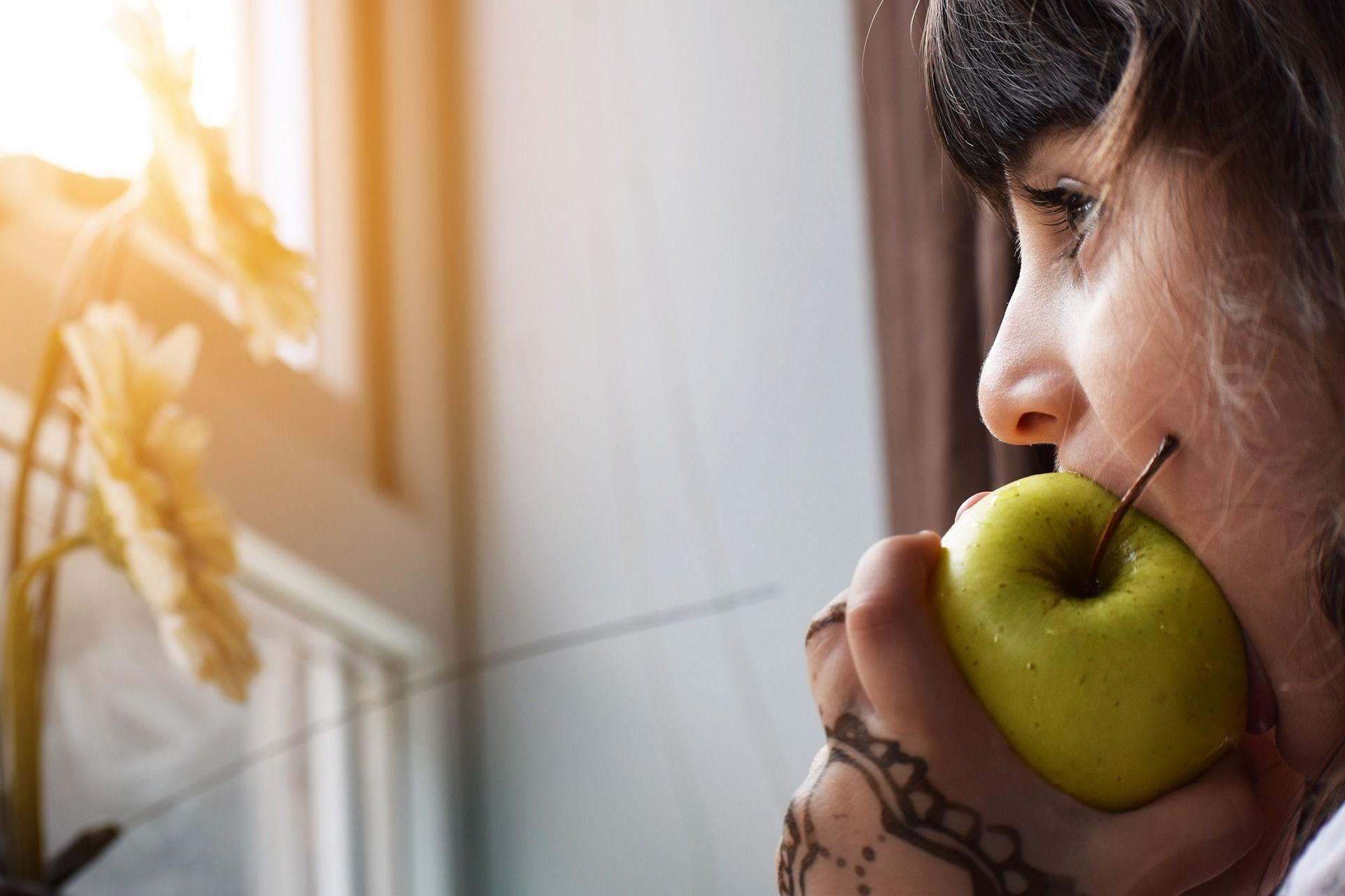 Chica joven comiendo manzana tras quitarse los alineadores invisalign. ¿Se puede comer con invisalign puesto? si