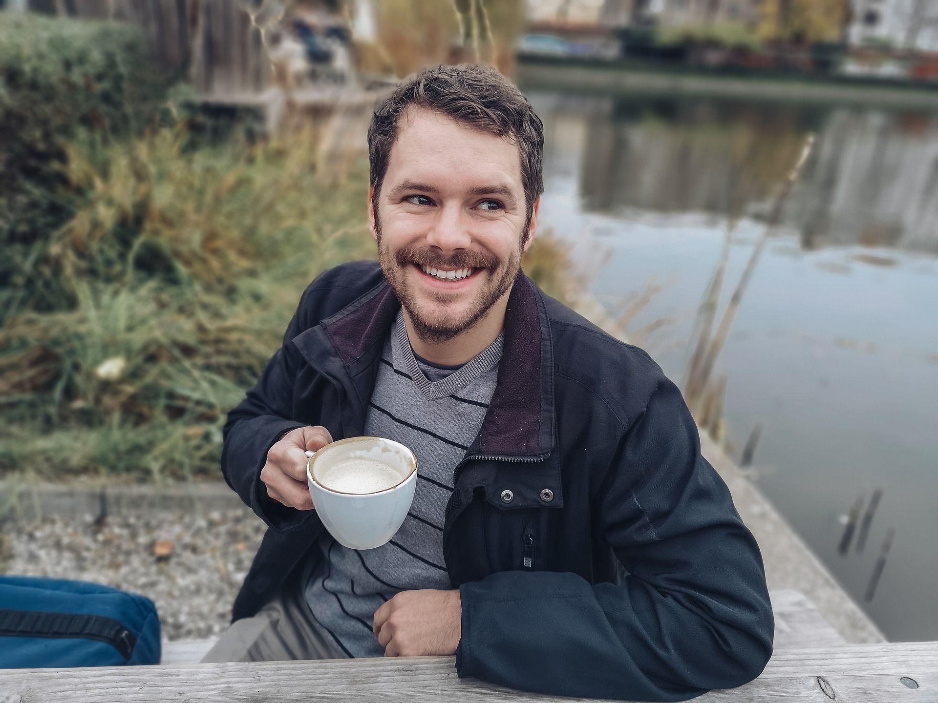 Hombre bebiendo café con alineadores invisibles invisalin. ¿se puede beber con invisalign?